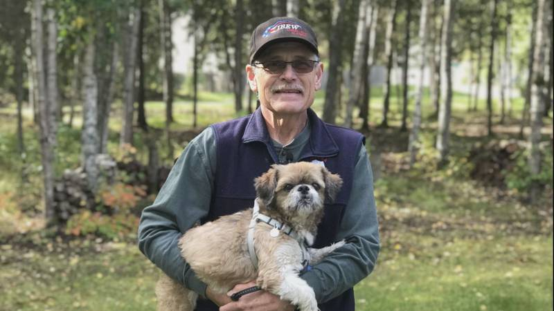 Mike Mitchell and his dog Chance pose at his home in Anchorage.