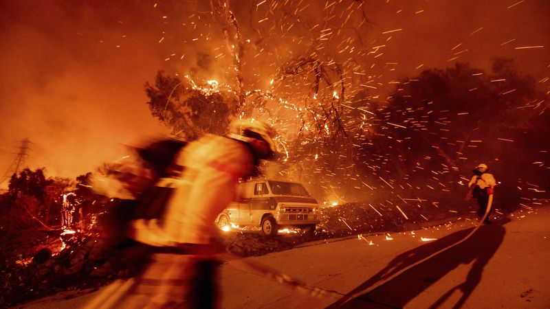 Firefighters battling the Bond Fire haul hose while working to save a home in the Silverado...