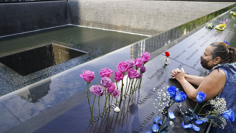 A mourner prays over the name cut-out of the deceased Emilio Pete Ortiz at the National...